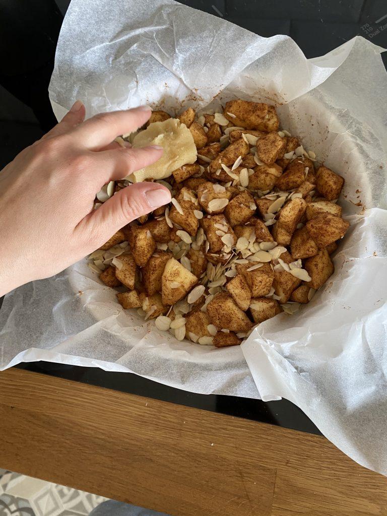 Colocar la masa sobre las manzanas haciendo bolitas. No hace falta que se cubran todas las manzanas.