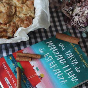crumble de manzana o apple pie junto al libro Una tarta de manzana llena de esperanza, decorado sobre una mantel de cuadros vichy grises y ramas de canela